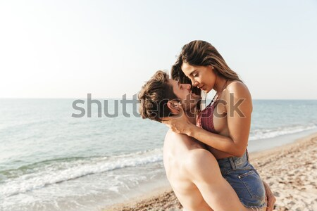 Happy couple sitting and hugging on pier Stock photo © deandrobot