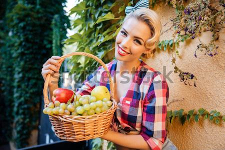Smiling pin up girl with basket of fruits eating apple Stock photo © deandrobot