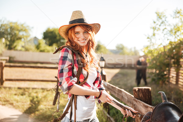 Stock photo: Happy woman cowgirl preparing saddle for riding horse