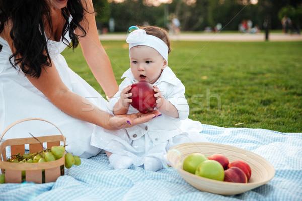 Cute nina comer grande manzana roja picnic Foto stock © deandrobot