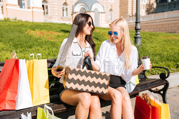 Two girls sitting on bench talking and showing new purchase Stock photo © deandrobot