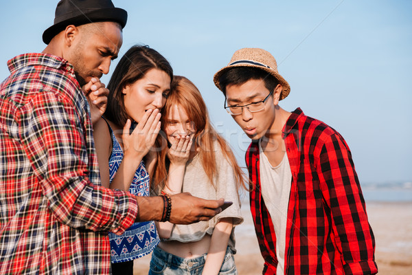 Amazed young people looking at screen of cell phone together Stock photo © deandrobot