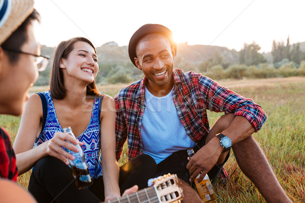Cheerful couple drinking beer and soda with friends outdoors Stock photo © deandrobot