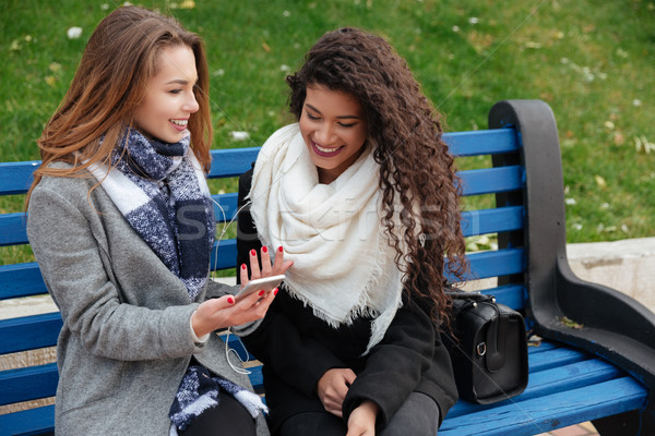 Fiatal női barátok mosolyog hallgat zene Stock fotó © deandrobot