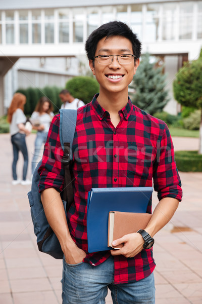 Happy asian young man student with backpack standing outdoors Stock photo © deandrobot