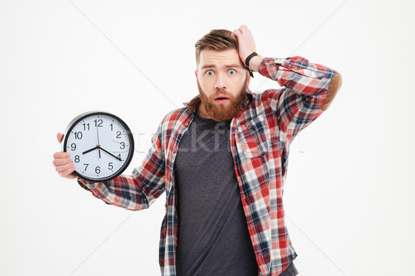 Worried man in checkered shirt holding and looking at camera Stock photo © deandrobot
