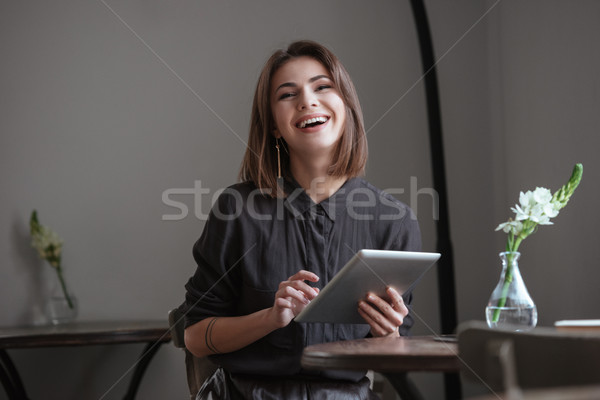 Funny lady sitting near window in cafe while using tablet Stock photo © deandrobot