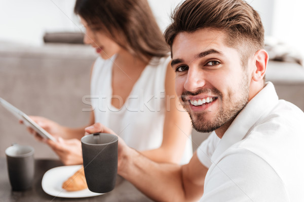 Man drinking coffee while his girlfriend using tablet on kitchen Stock photo © deandrobot