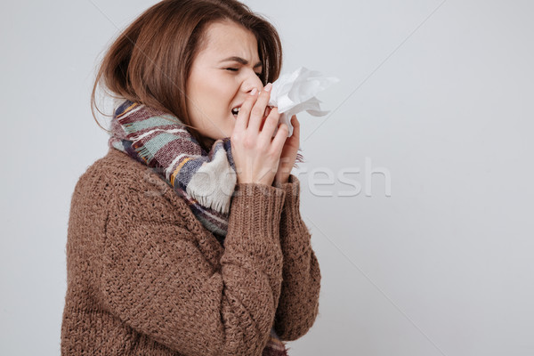 Sick young woman in sweater and scarf standing with napkin Stock photo © deandrobot
