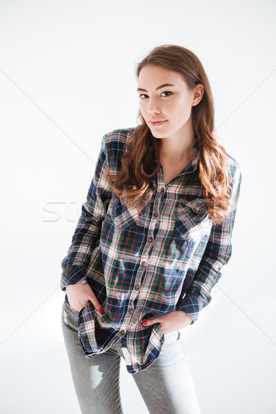 Happy cute young woman in plaid shirt and jeans Stock photo © deandrobot