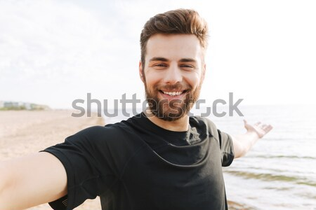 Young man in casual clothes walking at the beach Stock photo © deandrobot