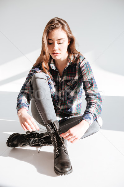 Young lady sitting on floor at studio and tie laces Stock photo © deandrobot