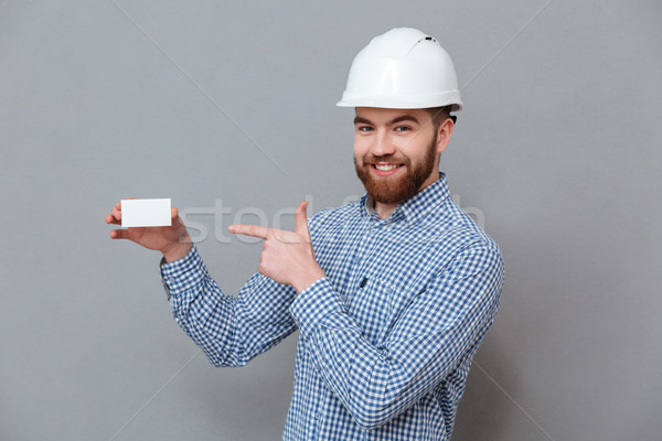 Cheerful bearded builder holding copyspace business card Stock photo © deandrobot