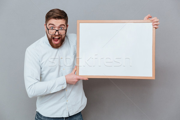 Shocked young bearded businessman holding copyspace board Stock photo © deandrobot
