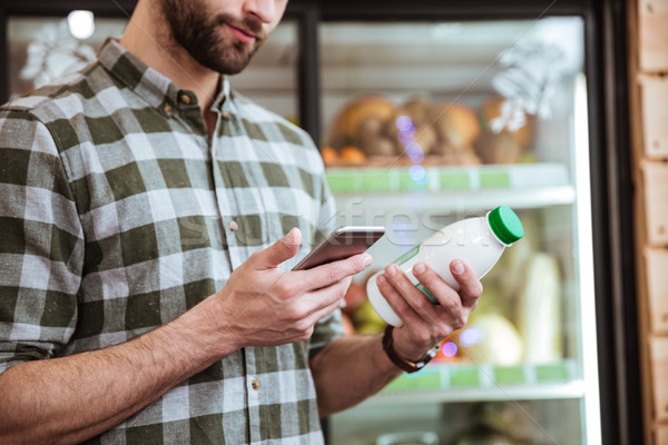 Man with bottle of milk using smartphone at grocery shop Stock photo © deandrobot