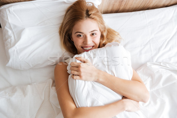 Top view of Happy woman emracing with pillow Stock photo © deandrobot