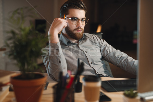 Young bearded web designer working late at night Stock photo © deandrobot