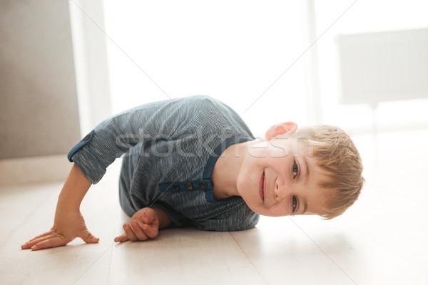 Kicsi fiú hazugságok padló néz kamera Stock fotó © deandrobot