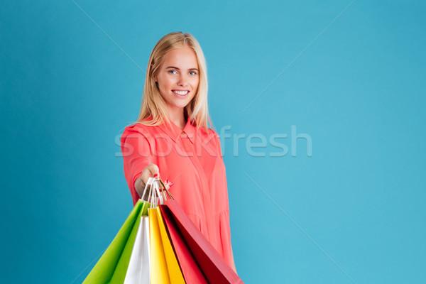 Mosolyog csinos nő mutat bevásárlótáskák kamerába portré Stock fotó © deandrobot