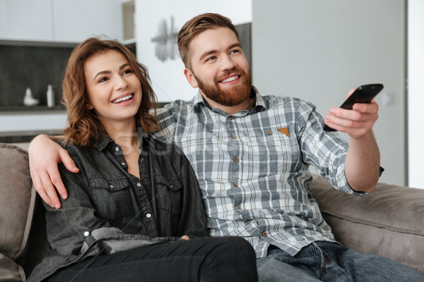 Happy loving couple sitting on sofa indoors and watching TV. Stock photo © deandrobot