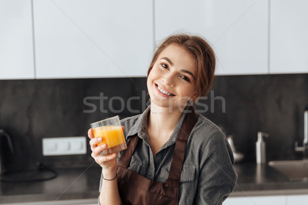 Cheerul woman standing in kitchen holding glass of juice Stock photo © deandrobot
