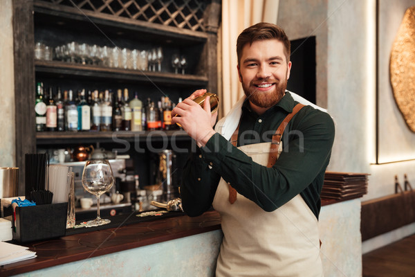 Cheerful young bearded man bartender standing in cafe. Stock photo © deandrobot
