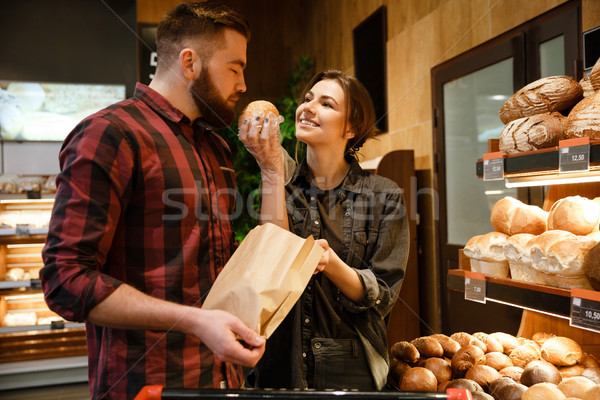 Loving couple in supermarket choosing pastries. Stock photo © deandrobot