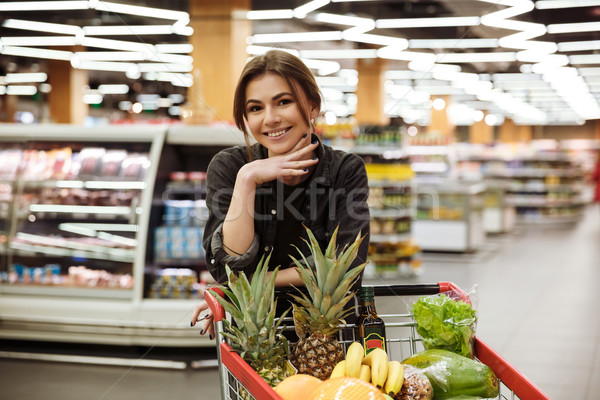 Happy woman in supermarket with shopping trolley Stock photo © deandrobot