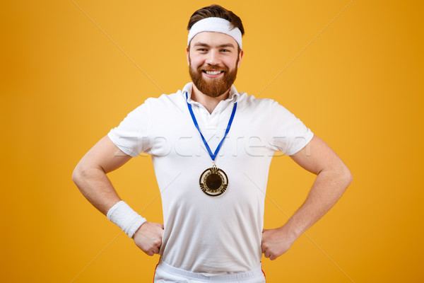 Happy young sportsman with medal looking at camera. Stock photo © deandrobot