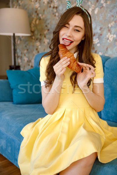 Smiling young pin-up lady eating croissant. Stock photo © deandrobot