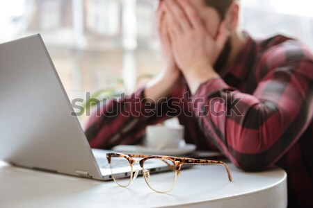 Bearded young man lies on hands in cafe. Focus on glasses. Stock photo © deandrobot