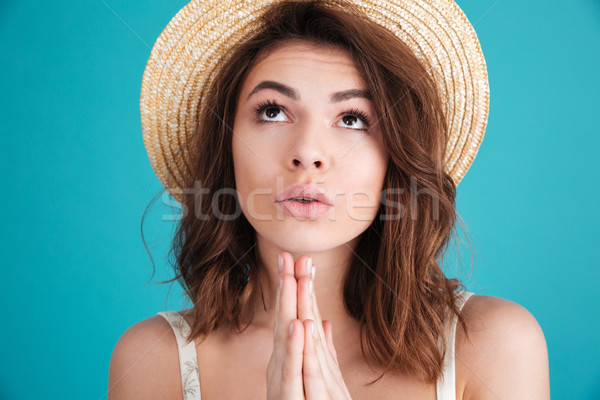 Young religious girl in straw hat praying for a vacation Stock photo © deandrobot