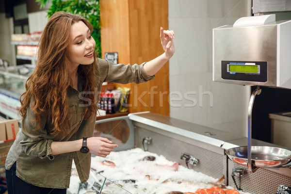 Side view of happy woman choosing fish Stock photo © deandrobot