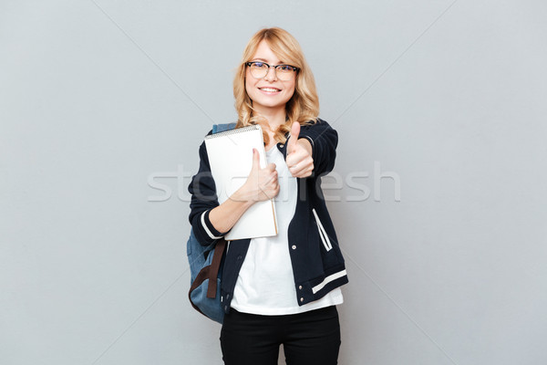 Cheerful young lady student holding notebook showing thumbs up. Stock photo © deandrobot