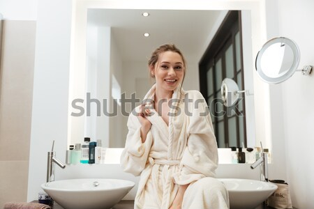 Stock photo: Happy beautiful young woman standing near the mirror in bathroom