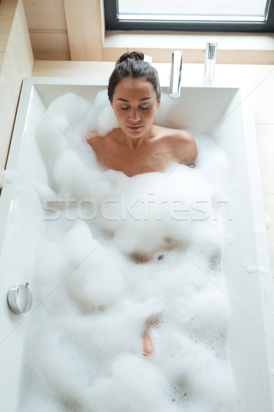 Peaceful young woman with closed eyes relaxing in bathtub Stock photo © deandrobot