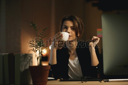 Concentrated young woman designer drinking coffee. Stock photo © deandrobot