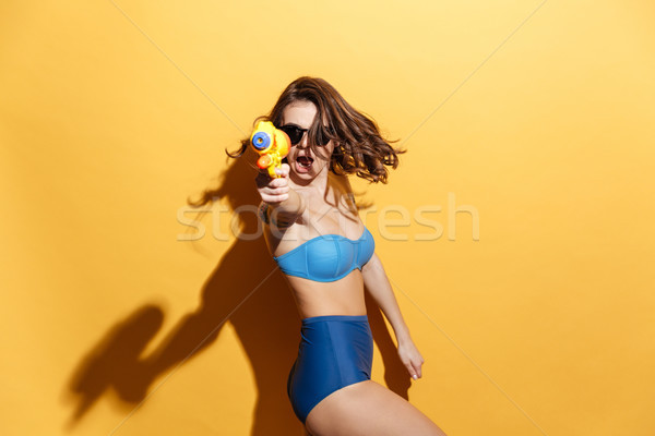 Emotional young woman in swimwear holding toy water gun Stock photo © deandrobot