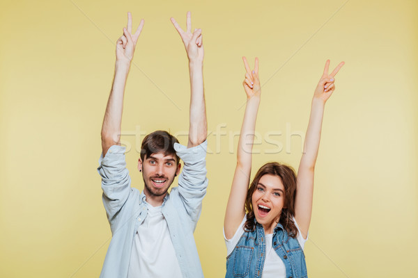 Happy brother and sister showing peace gesture Stock photo © deandrobot