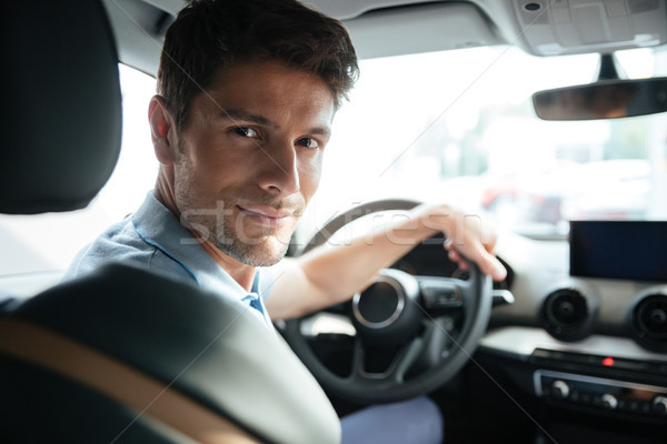 Stock photo: Handsome smiling male customer testing his new car