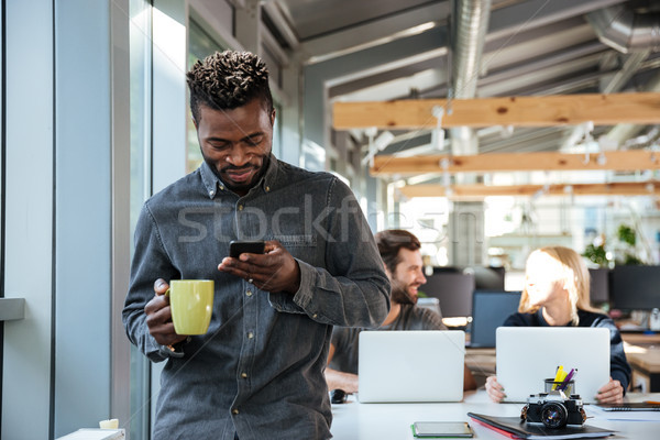 Smiling young african man standing in office chatting by phone Stock photo © deandrobot