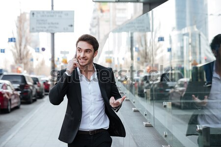Smiling young businessman walking near business center Stock photo © deandrobot