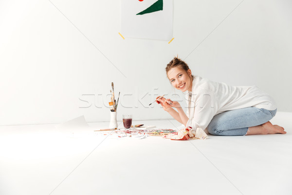 Happy young caucasian lady painter at workspace Stock photo © deandrobot
