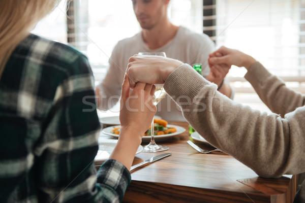 изображение люди , держась за руки молиться сидят обеденный стол Сток-фото © deandrobot