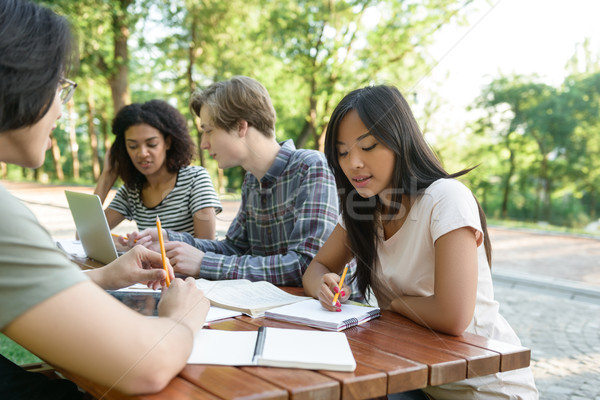 Multiethnic group of young students sitting and studying Stock photo © deandrobot