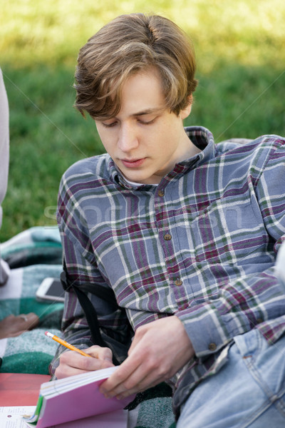 Smiling man student studying outdoors. Looking aside. Stock photo © deandrobot