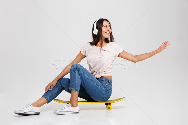 Young happy girl in white headphone with outstretched hand, sitt Stock photo © deandrobot