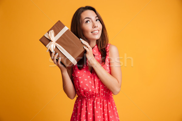 Intrigued runette woman in dress holding gift and looking up Stock photo © deandrobot
