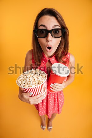 Top view of pretty young woman in 3d glasses eating popcorn, loo Stock photo © deandrobot