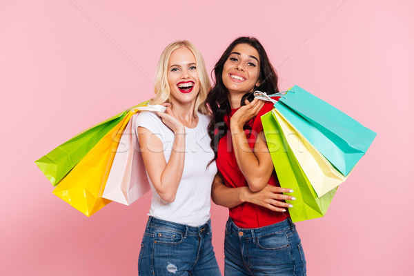 Two happy women holding packages on shoulders Stock photo © deandrobot
